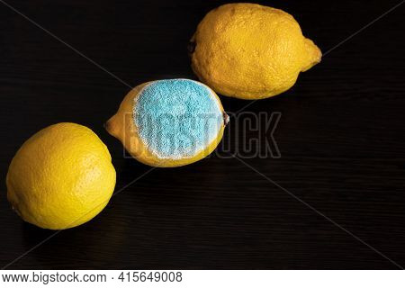 Three Whole Yellow Bright Lemons On A Dark Wooden Table. One Lemon In The Middle With Light Turquois