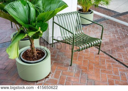 Green Metal Chair With Planting Along A Walkway. Rest Area Along A Pedestrain Way.