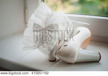 White Wedding Garter And White High Heel Shoes On The White Windowsill