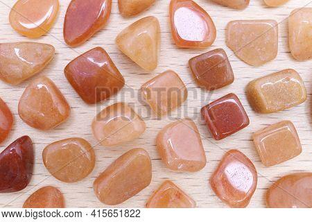 Red Aventurine Rare Jewel On Light Varnished Wood Texture. Sparse Mineral Pebbles Background.