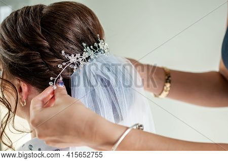 Bridesmaid Puts A Diadem On The Bride's Head