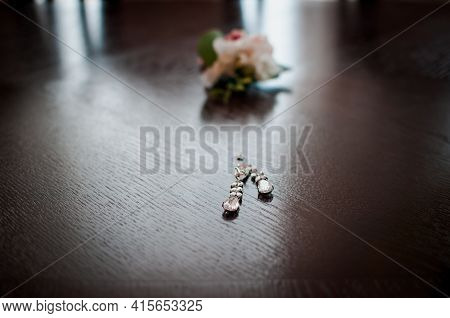 Pair Of Earrings And Flowers On The Brown Table
