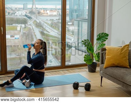Sportive lady with ponytail in green tracksuit sits on mat drinking water from bottle near panoramic glazed window in lodge