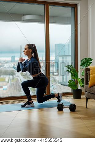 Slender brunette in turquoise jumpsuit in left leg squat pose near panoramic window with view on city in spring on glazed balcony