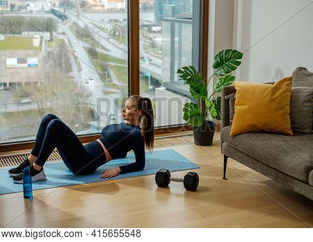 Sportive brunette in dark jumpsuit practices exercise with bent knees on blue mat near window with city view in spring in lodge