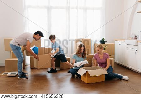 Beautiful Young Mother Sitting On Wooden Floor With Daughter Packing Stuff In Cardboard Boxes With H