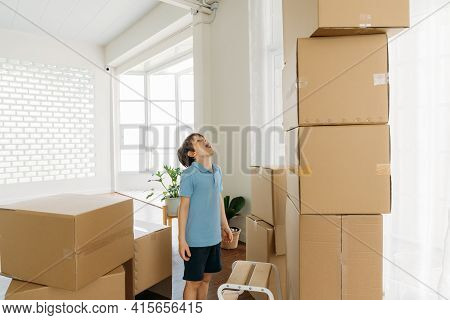 Excited And Shocked Caucasian Cute Little Boy Staring And Pile Of Cardboard Boxes During Shifting Ho
