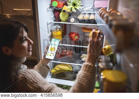 Beautiful Young Woman Standing Next To An Opened Refrigerator Door, Holding A Smart Phone And Orderi