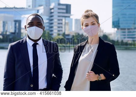 Two young intercultural managers in formalwear and protective masks looking at you while standing against riverside and skyscrapers