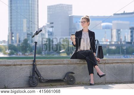 Young relaxed businesswoman with glass of coffee sitting by riverside with electric scooter near by against group of modern architecture