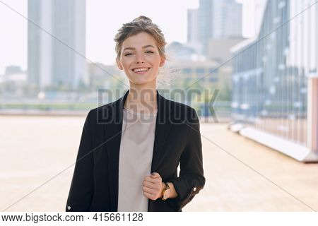 Young smiling blond businesswoman in formalwear standing in front of camera against cityscape with group of modern buildings
