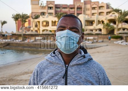 Portrait Of A Dark-skinned Man Of 40 Years In A Medical Mask On The Background Of The Resort Landsca