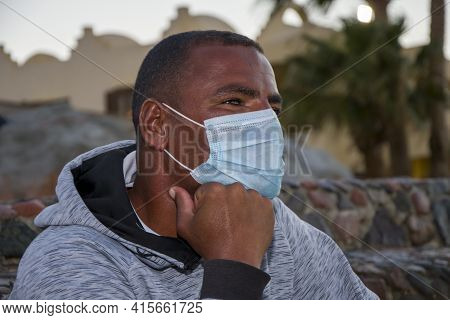 Portrait Of A Dark-skinned Man Of 40 Years In A Medical Mask On The Background Of The Urban Landscap