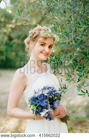 A Tender Bride With A Bouquet Of Blue Flowers In Her Hands Stands By Green Olive Branches In A Grove