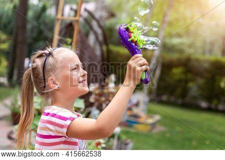 Portrait Of Cute Little Bond Kid Girl Enjoy Having Fun Play Blowing Soap Bubbles At Home Yard Garden