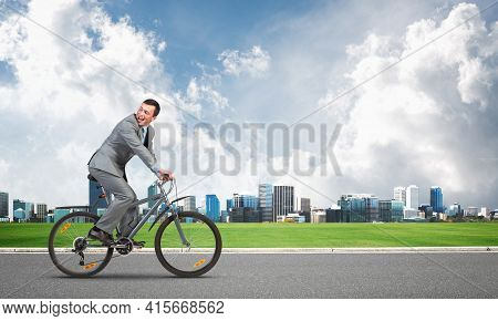 Businessman Commuting To Work By Bike. Man Wearing Business Suit Riding Bicycle On Asphalt Road. Han