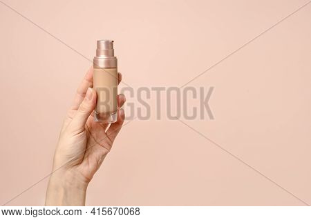 Hand Holding Makeup Liquid Found, Applying Foundation For Makeup. Woman's Hands With Neutral Manicur