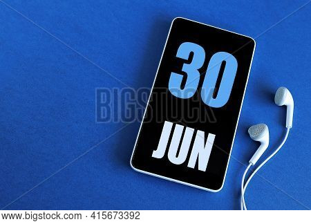 June 30. 30 St Day Of The Month, Calendar Date. Smartphone And White Headphones On A Blue Background