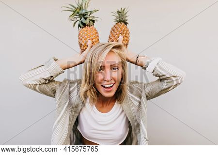 Good-humoured Young Lady Having Fun With Fruits. Pretty Laughing Girl Chilling In Studio During Phot