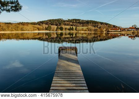 Empty Wooden Pier On Lake. Spring Pond Village In Background. Sunny Calm Idyllic Weather. Serenity S