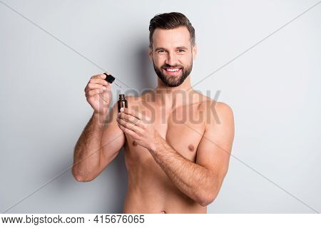 Portrait Of Attractive Fit Cheerful Nude Guy Holding In Hand Serum Nourishing Therapy Isolated Over
