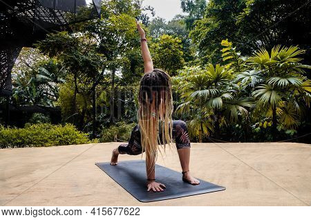 Caucasian Woman With Dreadlocks In Yoga Pose On A Black Mat