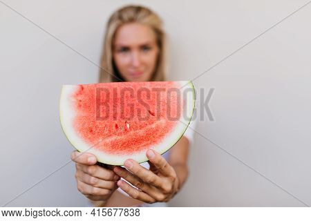Blur Portrait Of Interested Female Model Holding Watermelon. Good-humoured Girl With Blonde Hair Pos