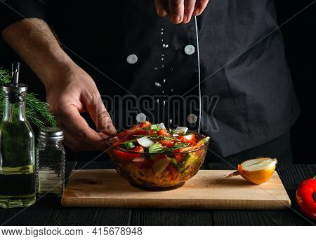 Chef Sprinkles Salted Fresh Vegetable Salad In A Plate On Wooden Table. Cooking Healthy Food In The