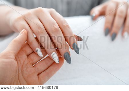 Beauty Master Manicurist Do Manicure To Client. Closeup Acrylic Artificial Nails Painted In Gray And