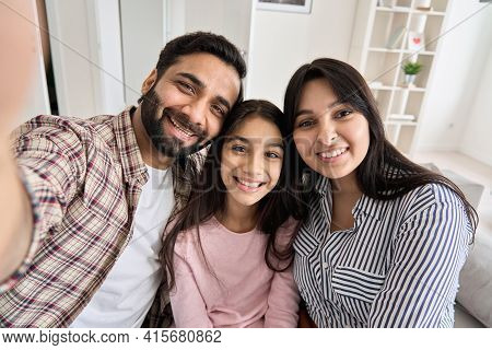 Happy Indian Couple And Teen Daughter Taking Selfie Looking At Phone Camera. Smiling Family With Chi