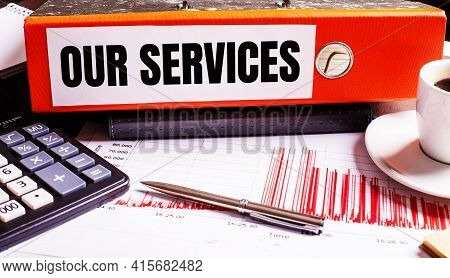 The Red Document Folder Says Our Services Next To The Coffee, Calculator And Pen.