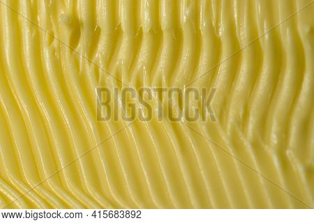 Food Themed Background Of Margarine. Shaped Into Detailed Yellow Grooves By A Serrated Kitchen Knife