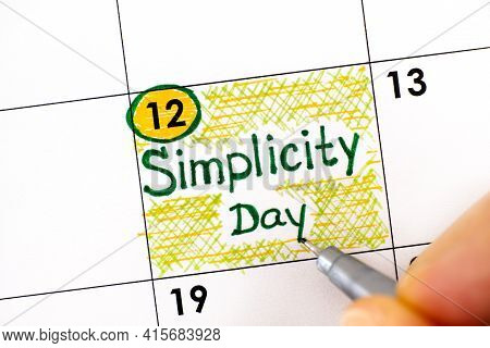 Woman Fingers With Pen Writing Reminder Simplicity Day In Calendar. July 12.