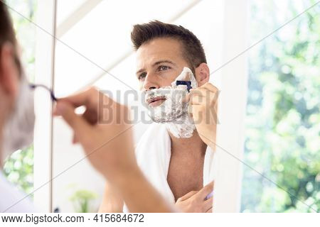 Handsome Man Shaving His Face In The Bathroom