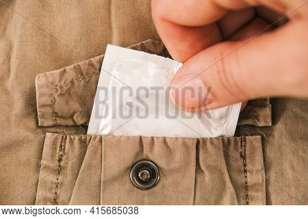 Woman Hand Taking Condom Out Of The Pocket Of A Beige Jacket. Focus On Condom. Close-up