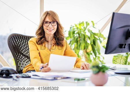 Confident Businesswoman Sitting At Desk And Working On Computer