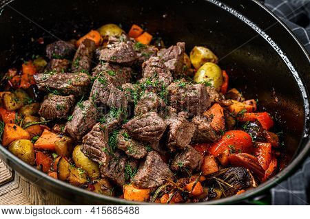 Beef Meat And Vegetables Stew In Black Baking Dish. Wooden Background. Top View