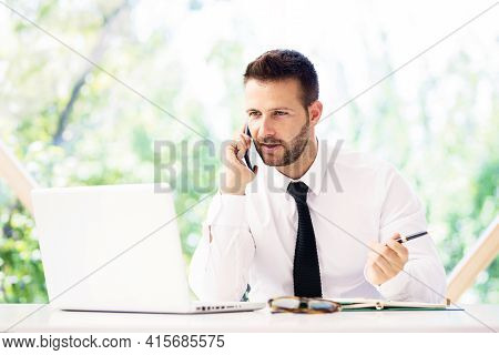 Shot Of Worried Businessman Talking With Somebody On His Mobile Phone While Sitting Behind Her Lapto