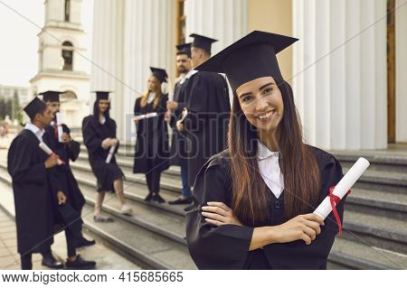 Graduate Girl With A Diploma In Her Hands On The Background Of Her Classmates.
