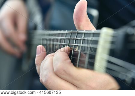 Rock Guitarist Fingers On Guitar Strings. Art And Music Concept. Close Up