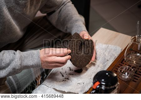 Close Up. A Tea Seller Breaks Off A Piece Of Strong Black Tea With A Tea Needle For Sale In A Tea Sh