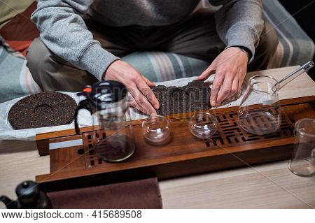 Set For A Tea Ceremony Close-up. A Man Using A Tea Needle Breaks A Tea Cake Of Strong Old Ripe Tea T