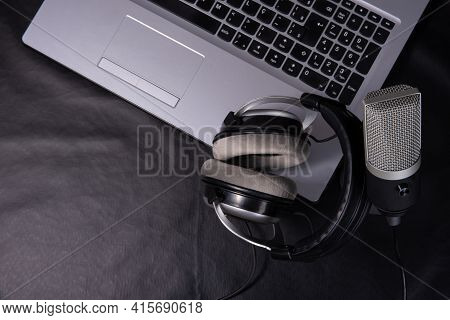 Home Work, Professional Condenser Microphone, Headphones And Computer On Dark Surface, Top View.