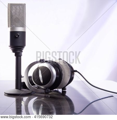 Professional Condenser Microphone And Headset On Reflective Surface And Light Background, Selective