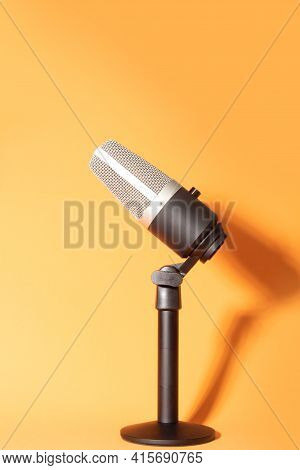 Professional Condenser Microphone With Pedestal Isolated On Orange Background Creating Shadow, Selec