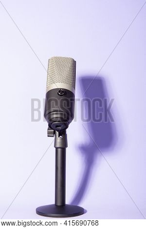 Professional Condenser Microphone With Pedestal Isolated On Violet Background Creating Shadow, Selec