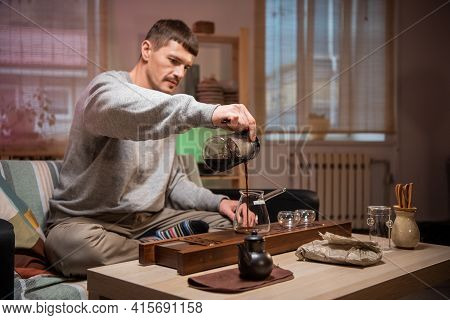 A Man Waits For Guests And Prepares Authentic Chinese Tea Using A Tea Ceremony Kit. Brews Ripe Raw T