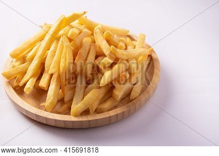 French Fries Placed On A Round Wooden Plate, White Background, Selective Focus.