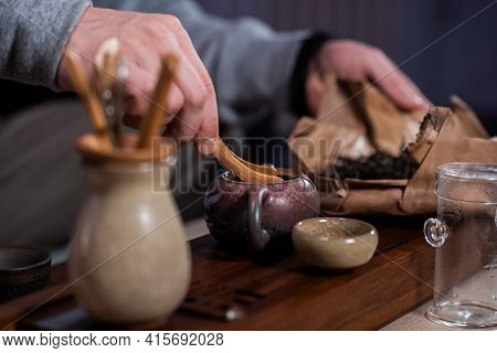 A Man Is Passionate About The Process Of Brewing Fragrant Black Pu-erh Tea. Throws The Tea Leaves In