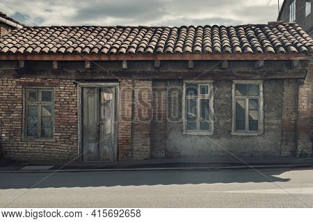 Facade Of The Old Abandoned Wrecked House With Tile Roof
